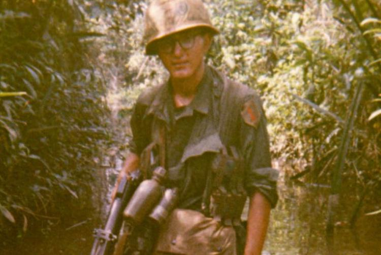 PFC Christopher D. Ammons searching canal for Viet Cong weapons