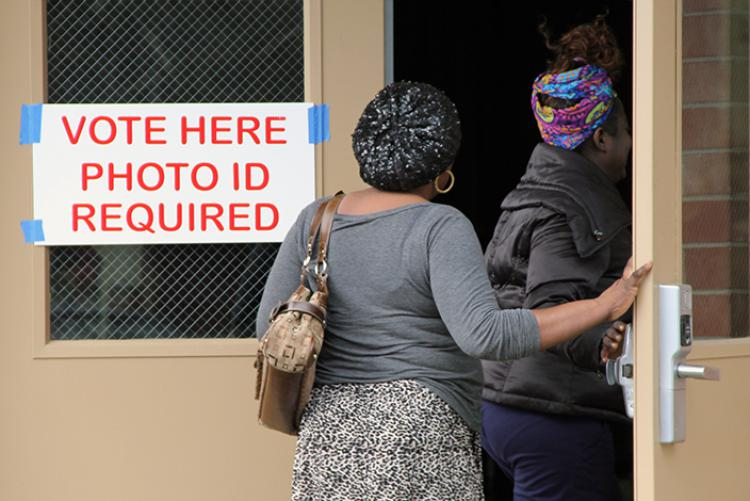Two women walking into a polling location with a sign on the door that says