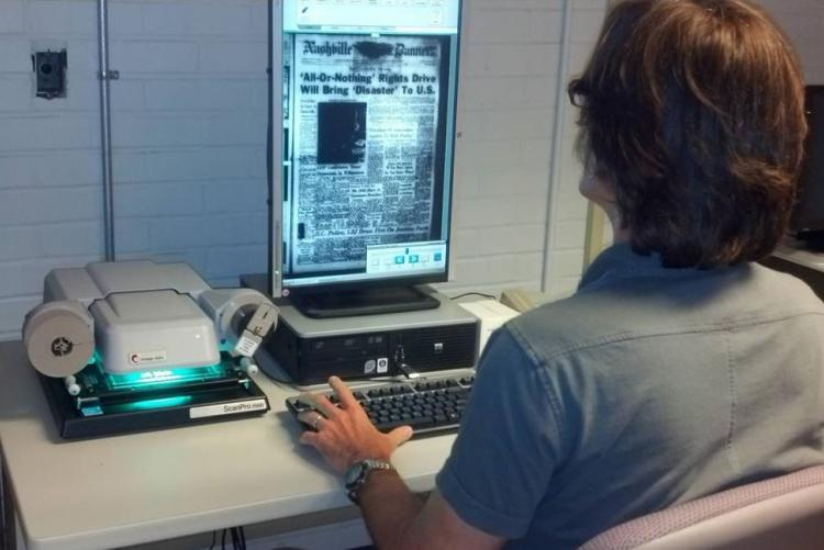Library and Archives patron using microfilm reader/scanner