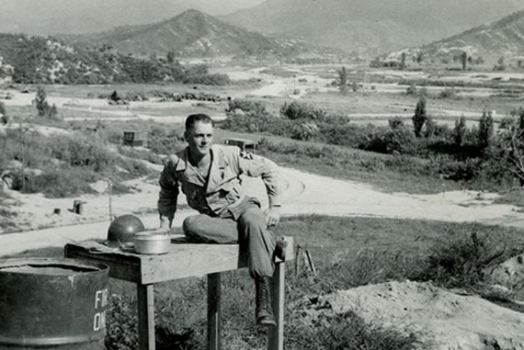 "Brock sitting on washstand at ""The Hook"" base camp"
